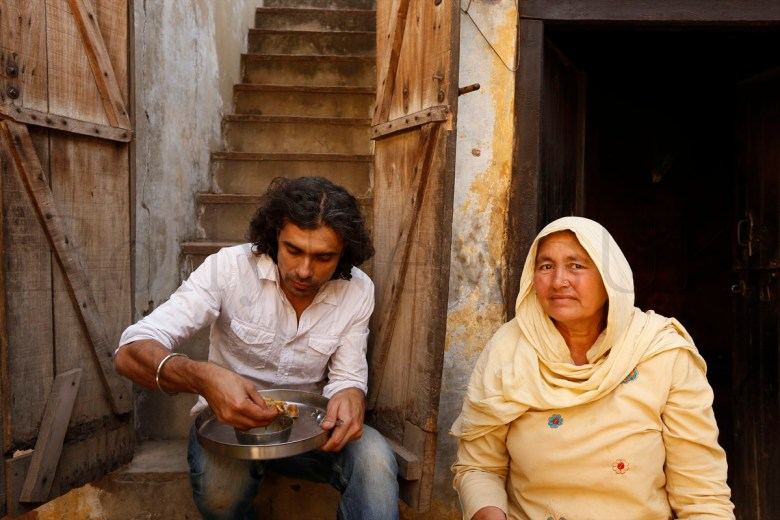 Imtiaz Ali enjoys a simple meal cooked by the resident of the house he was shooting in for HIGHWAY, Village Dayalpur-Haryana